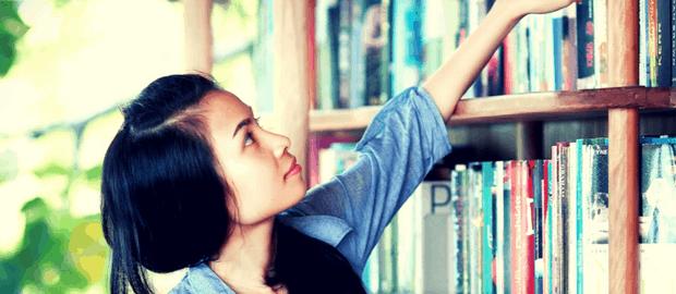 estudante jovem alcança livro em prateleira