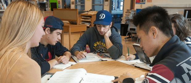jovens estudando ao redor de uma mesa